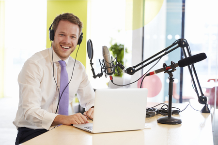 Young man recording a podcast smiling to camera, close up