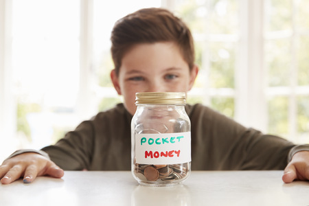 Boy Saving Pocket Money In Glass Jar At Home