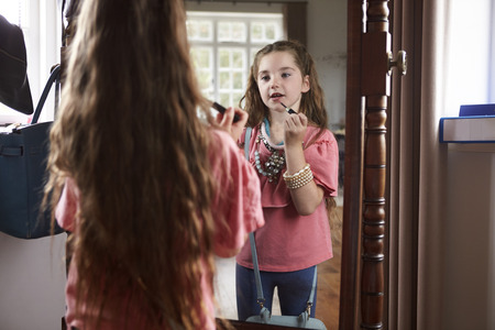Young Girl Playing Dressing Up Game In Front Of Mirror At Home Banque d'images
