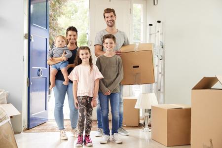 Portret van familie met vakken in nieuw huis op bewegende dag