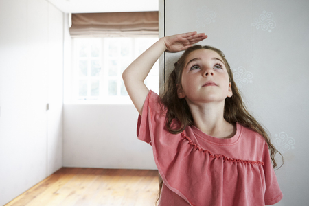 Girl Measuring Height Standing Against Wall At Home