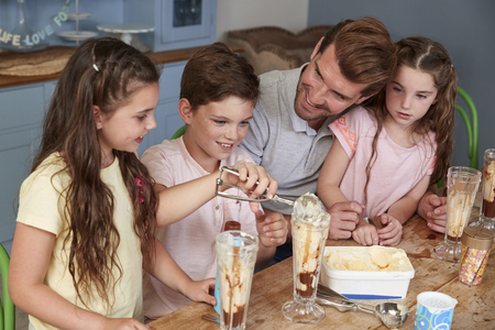 Father Making Ice Cream Sundaes With Children At Home Banque d'images