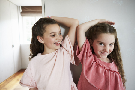 Two Sisters Comparing Height Measured Against Wall Stock Photo
