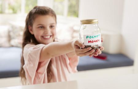 집에서 유리 항아리에있는 소녀 돈을 절약 소녀