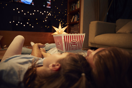 Father And Daughter Enjoying Movie Night At Home Together