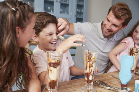 Father Making Ice Cream Sundaes With Children At Home Stockfoto