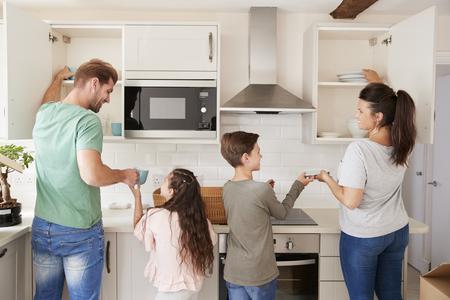 Kinderen helpen om servies in keukenkastjes weg te zetten
