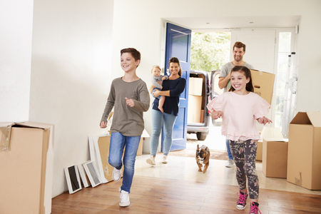 Family Carrying Boxes Into New Home On Moving Day Standard-Bild