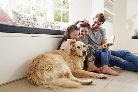 Libro de lectura del padre con hijo e hija y perro mascota en casa Foto de archivo