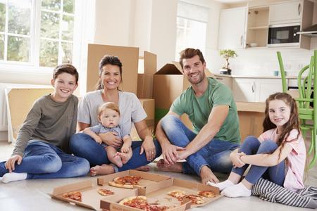 Portret van familie vieren verhuizen naar nieuw huis met pizza