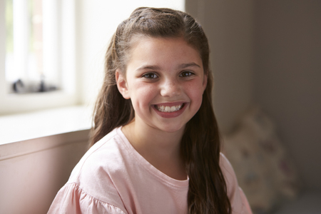 Portrait Of Smiling Young Girl Sitting On Window Seat At Home