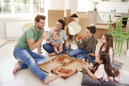 Family Celebrating Moving Into New Home With Pizza Banque d'images