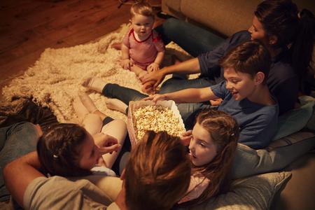 家族一緒に夜自宅で映画を楽しんでのオーバー ヘッド ビュー 写真素材