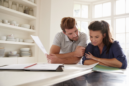 Couple Looking At Domestic Finances At Home Together