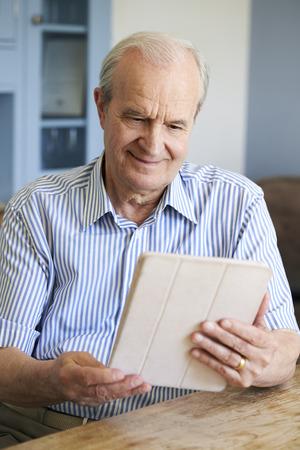テーブルでを使用してデジタル タブレットを家で座っている年配の男性