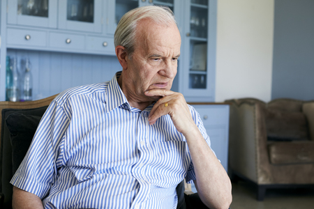 Senior Man Sitting In Chair At Home Suffering From Depression Standard-Bild