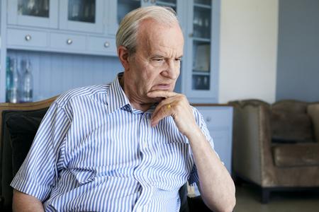Älterer Mann, der zu Hause im Stuhl leidet unter Krise sitzt