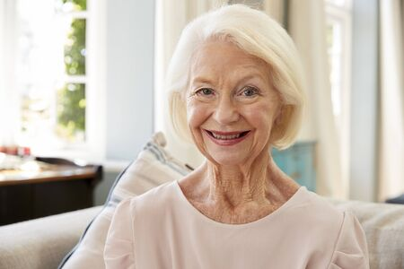 Portrait Of Smiling Senior Woman Sitting On Sofa At Home 写真素材