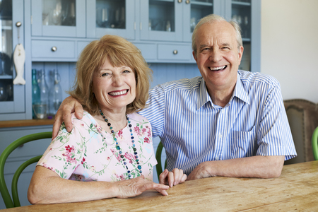 Portrait Of Smiling Senior Couple Sitting On Sofa At Home 版權商用圖片 - 90312323