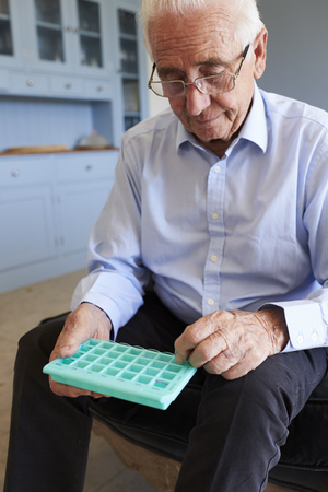 Senior Man At Home Using Pill Organiser For Medication Stock Photo