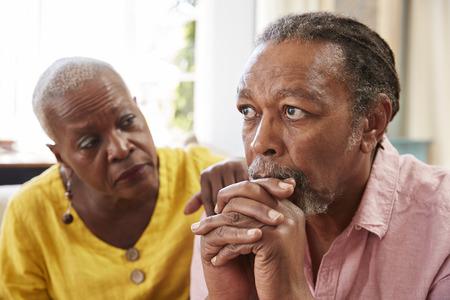Ältere Frau, die Mann mit Krisen zu Hause tröstet Standard-Bild
