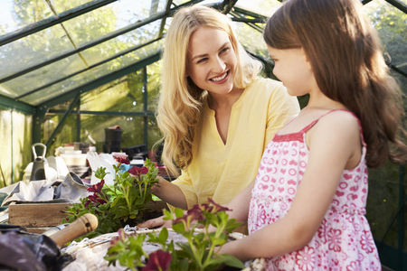 Mother And Daughter Planting Hanging Basket In Greenhouse Stock Photo