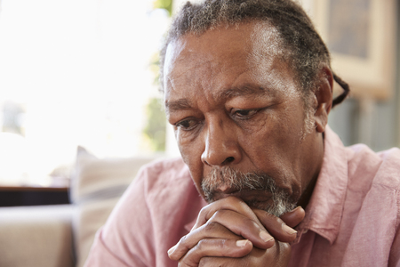 Starszy mężczyzna siedzi na kanapie w domu cierpiących na depresję Zdjęcie Seryjne