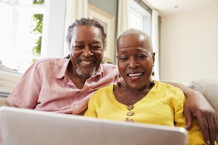 一緒に自宅のノート パソコンを使用してソファに座っている年配のカップル