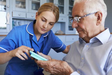 Nurse Helping Senior Man To Organize Medication On Home Visit