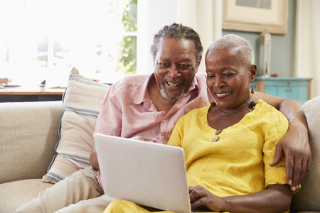 Senior Couple Sitting On Sofa Using Laptop At Home Together Stock Photo - 90340483