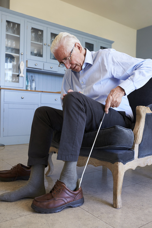 年配の男性の靴に入れて援助を使用して椅子に