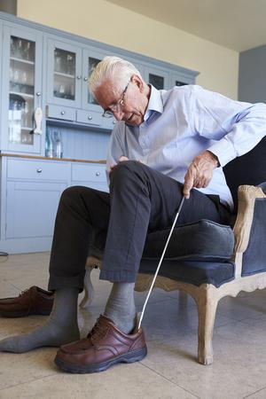 Lterer Mann im Stuhl unter Verwendung der Hilfe, zum des Schuhs zu setzen Standard-Bild - 90330181