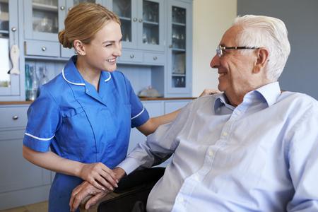 看護師が家庭訪問で椅子に座っている年配の男性と話しています。 写真素材