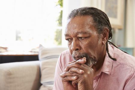 Hogere Mens die op Bank zit die thuis aan Depressie lijdt Stockfoto