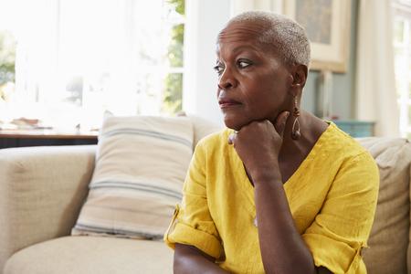 Ältere Frau, die zu Hause auf dem Sofa leidet unter Krise sitzt