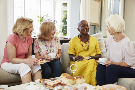 Senior Female Friends Enjoying Afternoon Tea At Home Together Archivio Fotografico