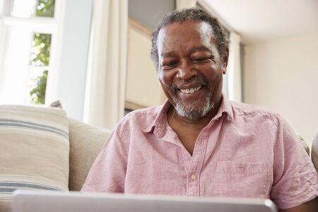 一緒に自宅のノート パソコンを使用してソファに座っている年配の男性