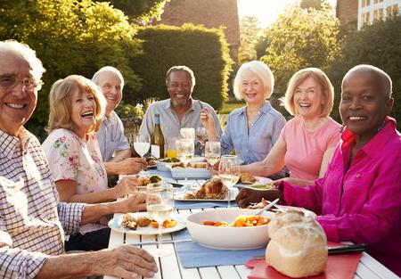 Portrait Of Senior Friends Enjoying Outdoor Dinner Party At Home Stock fotó