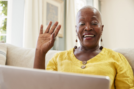 Senior Woman Using Laptop To Connect With Family For Video Call Imagens