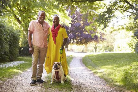 Portrait Of Senior Couple Walking Pet Bulldog In Countryside Stock Photo