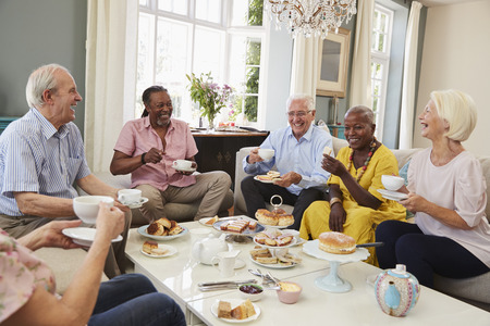 Group Of Senior Friends Enjoying Afternoon Tea At Home Together Stockfoto