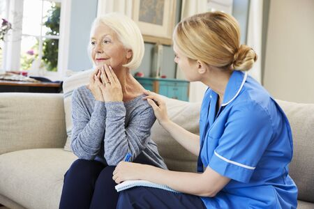 Community Nurse Visits Senior Woman Suffering With Depression Stock Photo