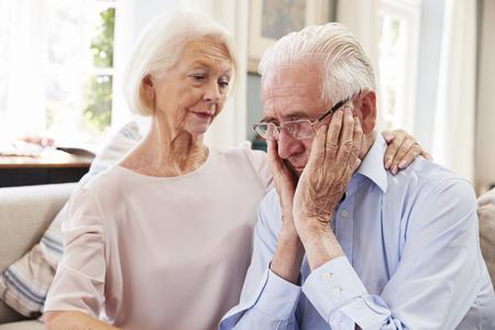 Donna senior che conforta uomo con la depressione a casa