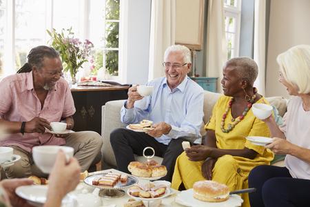 Gruppe ältere Freunde, die zu Hause Nachmittagstee zusammen genießen