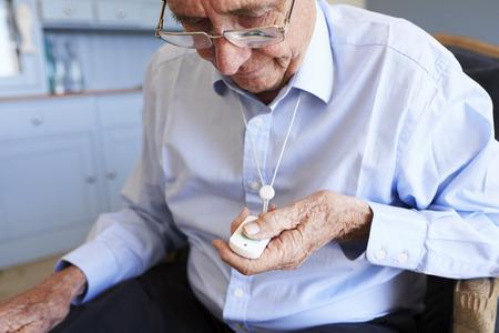 Uomo senior a casa facendo uso del pulsante di chiamata dell'allarme di emergenza Archivio Fotografico - 90312145