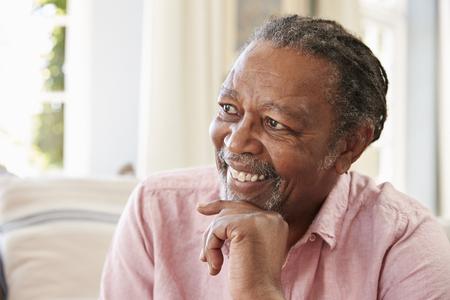 Smiling Senior Man Sitting On Sofa At Home 스톡 콘텐츠