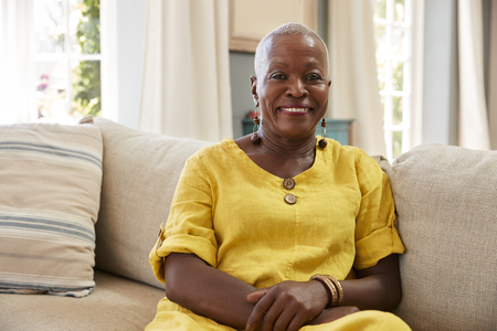 Portrait Of Smiling Senior Woman Sitting On Sofa At Home Stock Photo