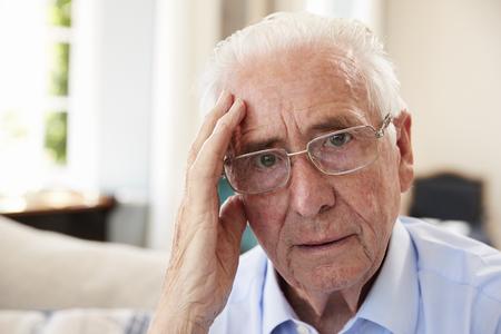 Portrait Of Senior Man Sitting On Sofa Suffering From Depression