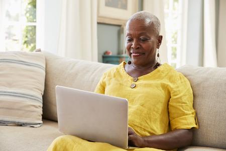 Haute femme assise sur un canapé à l'aide d'un ordinateur portable à la maison ensemble Banque d'images - 90788594