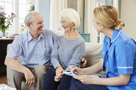 Female Community Nurse Visits Senior Couple At Home